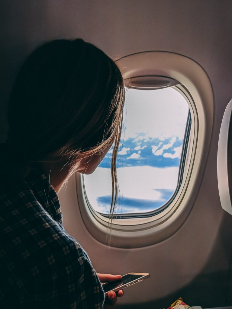 girl looking through an airplane window