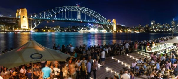people sitting and standing near bridge during nighttime in Sydney